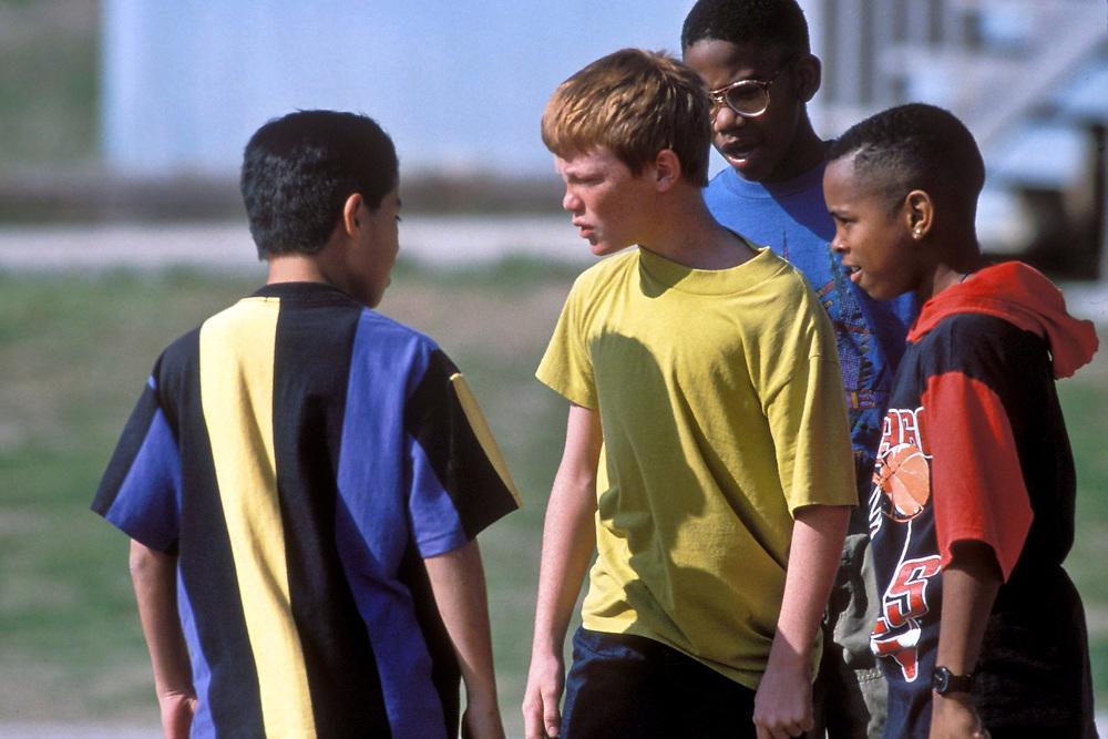 Austin, Texas: Multi-ethic Elementary schoolboys argue on playground. ©Bob Daemmrich