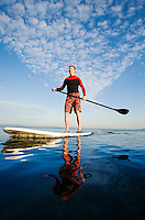 An athletic man paddling out on Elliott Bay / Puget Sound in the early morning.