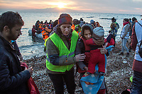 LESVOS, GREECE - FEBRUARY 09: A volunteer helps a mother holding her young son after getting off a dinghy on which they crossed the Aegean sea from the Turkish coast with other dozens of refugees on February 09, 2015 in Lesvos, Greece. Photo: © Omar Havana. All Rights Are Reserved