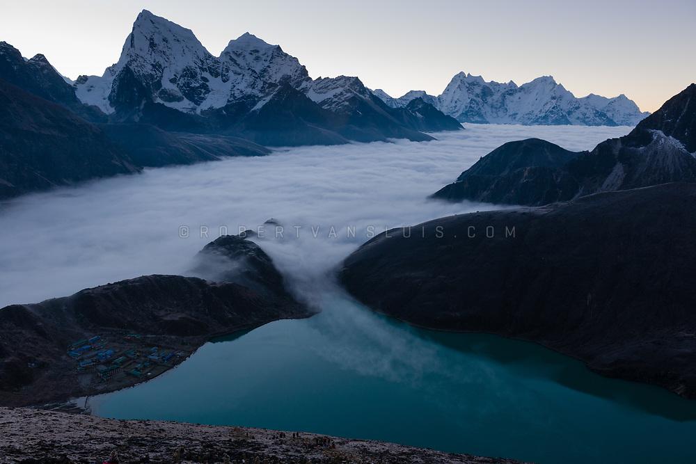 In the Nepal Himalaya, a sea of clouds covers the Ngozumpa Glacier in predawn light. Photo © robertvansluis.com