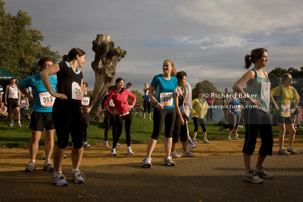 Amateur running club athletes warm-up with group aerobics before a 10k race in Dulwich Park, South London.