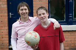 Father and son; arm in arm smiling; after a game of football,