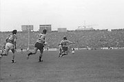 Dublin slides in to get a kick on the ball during the All Ireland Senior Gaelic Football Final, Kerry v Dublin in Croke Park on the 28th September 1975. Kerry 2-12 Dublin 0-11.