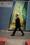 A Londoner walks beneath an illustration of future office development of the Leadenhall Building by the Brookfield Multiplex construction company at 100 Bishopsgate in the financial district City of London. Looking up to see the rise of the mammoth buildings already in use, the newest site grows upwards to occupy the empty location. The Brookfield Multiplex builds, engineers, develops and maintains property and infrastructure around the world. Over the past five decades we have successfully completed over 726 major projects, with a combined value of over $27.5 billion in Australasia, Europe, the Middle East and Asia. The 100 Bishopsgate development will become one of the most significant new commercial office buildings in the City comprising 3 buildings totalling c815,000sf NIA.