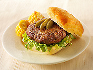 BBQ beef burger in a chabatta roll with gherkins & BBQ sweet corn on a  plate photos. Funky Stock Photos