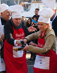 London, February 17th 2015. Members of Parliament put their dignity aside for a bit of fun as they compete in the annual Parliamentary Pancake Race in Victoria Tower Gardens adjacent to the House of Lords.  PICTURED: Daily and Sunday Politics Editor Robbie Gibb and Sky News' Sophie Ridge change over in the relay race.