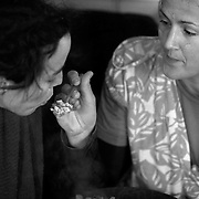 """Beth M. (right) feeds Adah F. a spoonful of  rice and lentils while ating lunch during Crop mob at Eatable Earthscapes Farm in Pittsboro, NC. The """"Mob"""" is as much about socializing, sharing ideas and thoughts as it is accomplishing work and chores."""
