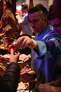 Flushing, NY - February 25, 2017. Rodrigo Duarte from Caseiro e Bom Gourmet House in Newark, N.J., slicing and serving cured ham from Portugal's Alentejo at the 2017 Charcuterie Masters at Flushing Town Hall. The hams are cured here from pigs imported from Portugal.