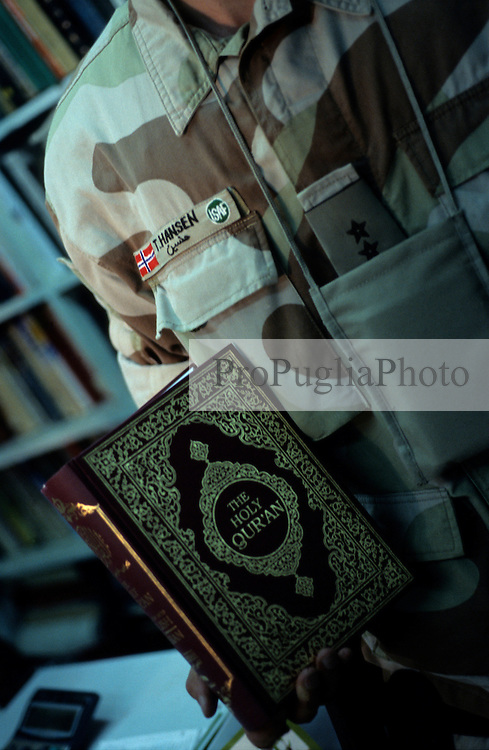 A Danish Army officer holding a copy of the Holy Qur'an...According to Muhammad Rias, the shop-owner, the Danish buy the Qur'an most...Kabul,  Shahm Book Co. 14 August 2005.