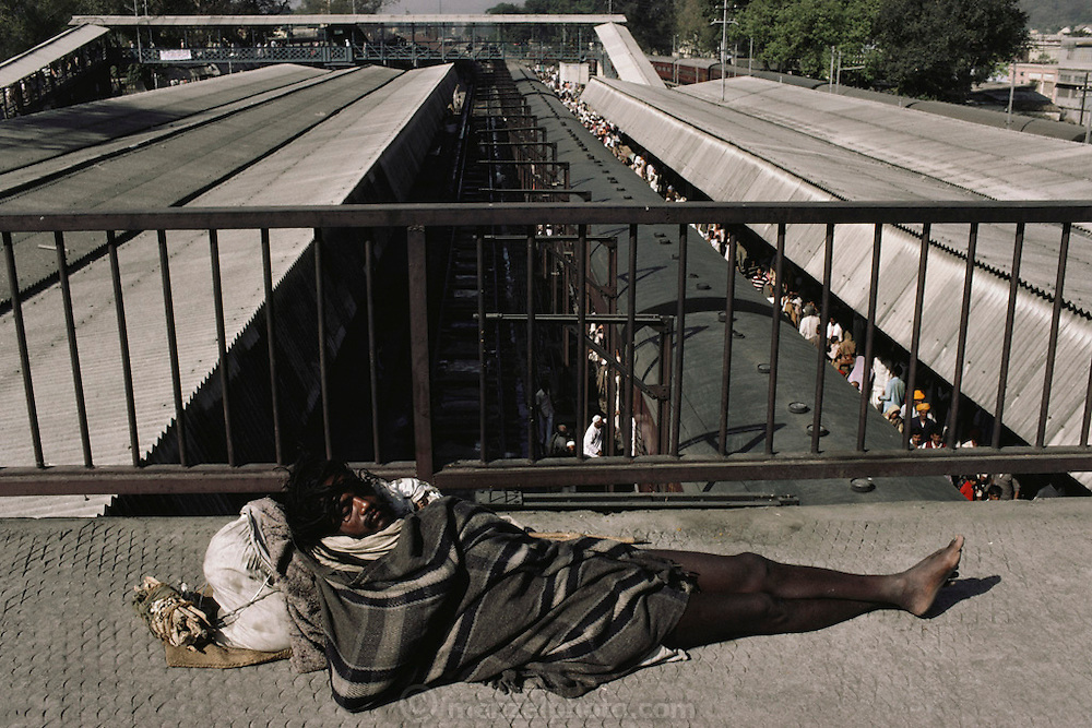 A pilgrim sleeps on the walkway over other pilgrims jamming the trains in Hardiwar station. Every 12 years, millions of devout Hindus celebrate the month-long festival of Kumbh Mela by bathing in the holy waters of the Ganges at Hardiwar, India. Hundreds of ashrams set up dusty, sprawling camps that stretch for miles. Under the watchful eye of police and lifeguards, the faithful throng to bathe in the river.