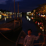 A local man relaxes on his boat besides the lantern lit waterfront, Hoi An, Vietnam. Hoi An is an ancient town and an exceptionally well-preserved example of a South-East Asian trading port dating from the 15th century. Hoi An is now a major tourist attraction because of its history. Hoi An, Vietnam. 5th March 2012. Photo Tim Clayton