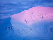 Large rock and ice formations, coloured by the setting sun, on the top of Mount Storsteinen in Tromso, Norway