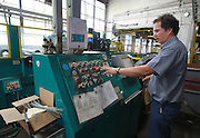 Paul Hefner, lead man and shear machine operator, activates the shear machine, which cuts huge rolls of sheet metal to length for manufacturing gas stoves. The Belleville manufacturing firm is celebrating its 80th anniversary.