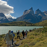 Hikers beside Lake Nordenskjold, below the Horns of Paine in  Torres del Paine National Park, Chile.