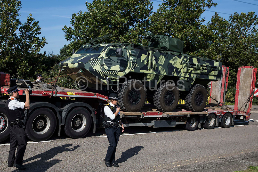 Metropolitan Police officers monitor a convoy of trucks delivering military equipment to ExCeL London for the DSEI 2021 arms fair on 8th September 2021 in London, United Kingdom. The third day of week-long Stop The Arms Fair protests outside the venue for one of the worlds largest arms fairs was themed around demilitarising education.