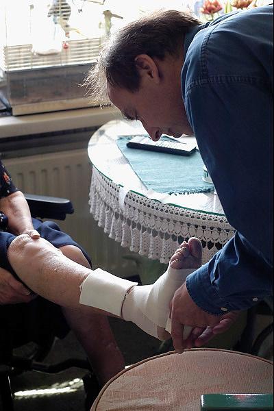 Nederland, Nijmegen, 27-3-2003..Huisarts op visite bij oudere patient verbindt een wond aan het been. Gezondheidszorg, basiszorg, eerstelijns hulpverlening...Foto: Flip Franssen