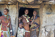 Three Datooga women and a child stand at the entrance to their hut Photographed in Lake Eyasi Tanzania