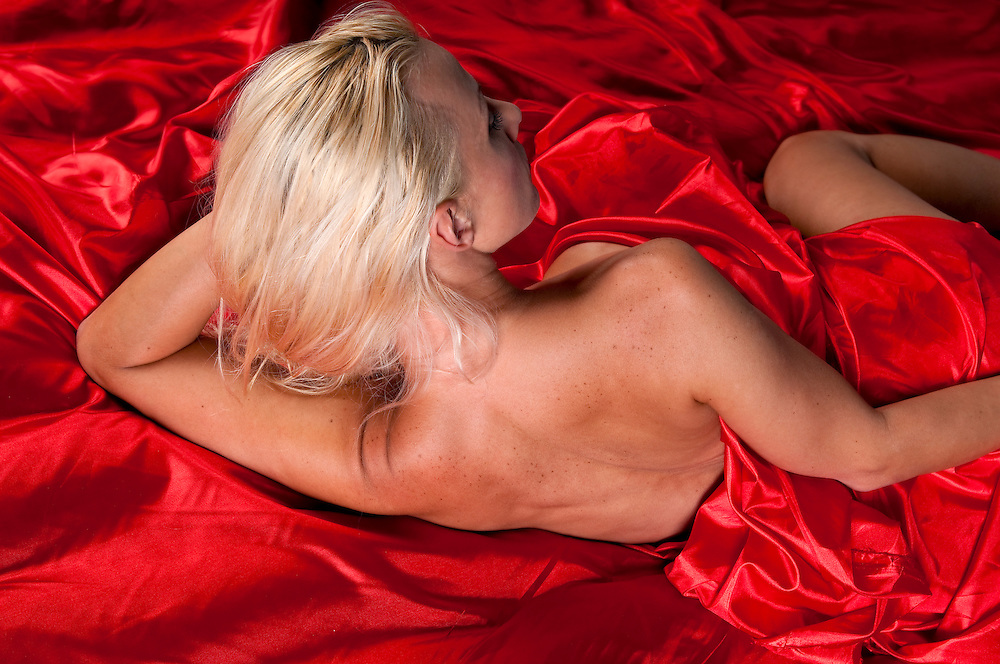 Young glamour model posing naked in red silk sheets.