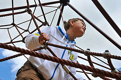 12 yr old boy playing on a rope structure at Beale Park wildlife park, Berkshire. MR