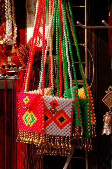Merchant display's purses at shop in China Town, San Francisco, California.