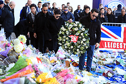Aiyawatt Srivaddhanaprabha (front) and family members walk through tributes to lay a wreath in memory of Vichai Srivaddhanaprabha, who was among those to have tragically lost their lives on Saturday evening when a helicopter carrying him and four other people crashed outside King Power Stadium.