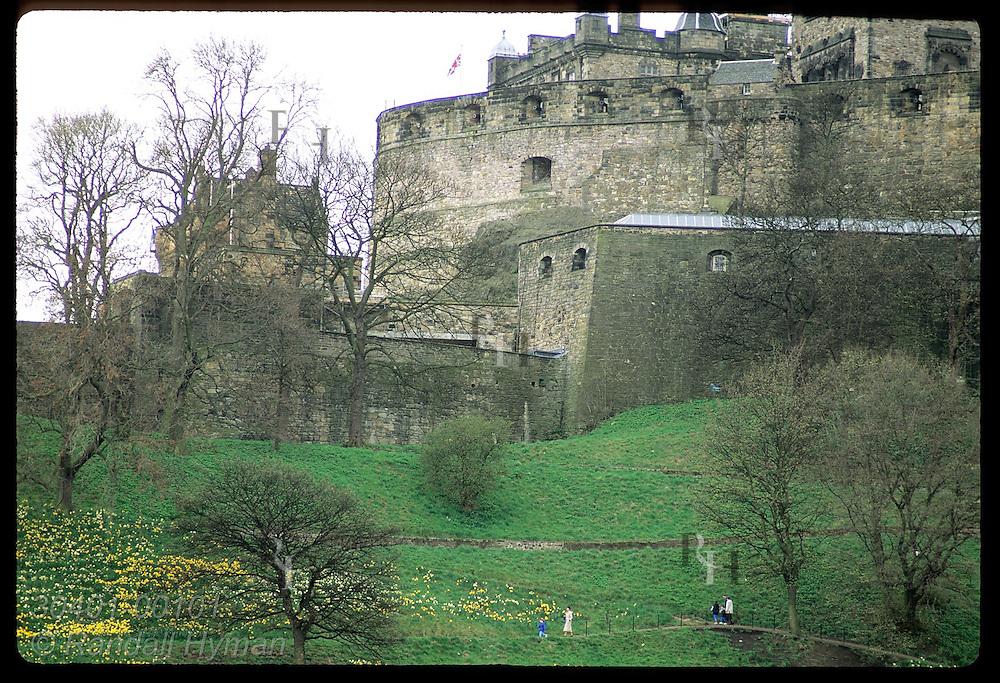 Family walks path beneath Edinburgh Castle's massive stone walls on a spring afternoon; Edinburgh Scotland