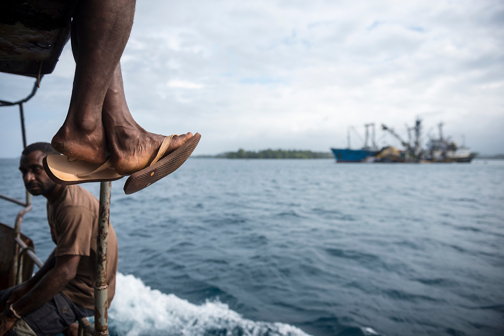 Madang, Papua New Guinea - August 10, 2017: A small passenger and cargo vessel traveling from Karkar Island to Madang sails past tuna trawlers anchored in Sek Harbor, where trawlers drop off their catch of tuna. Madang is home to a large tuna cannery.