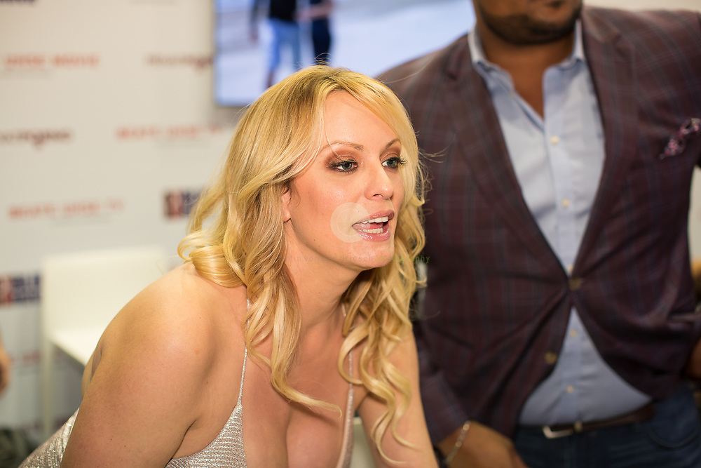 Berlin Expo Center, Berlin, GERMANY, 12.10.2018. Former adult actress Stephanie Clifford, known as Stormy Daniels signs an autograph for a visitor during the Venus Erotic Trade Fair in Berlin, Germany, 12 October 2018. Daniels, who allegedly had a sexual encounter in 2006 with US President Donald J. Trump, sued the president over a hush money agreement she signed before he ascended to the Oval Office. The Venus Berlin Fair is among the largest international erotic trade fairs, with more than 250 exhibitions from 40 countries and 30,000 visitors. <br /> <br /> Messegelaende unterm Funkturm, Berlin, DEUTSCHLAND, 12.10.2018. Stormy Daniels auf der VENUS 2018: Pornostar Sot Messegelaende unterm Funkturm, Berlin. 12.10.2018. Stormy Daniels auf der VENUS 2018: Stormy Daniels gibt Autogramme am Stand von Beate Uhse TV.  Daniels erlangte Bekanntheit durch eine angebliche Affaere mit US-Praesident Donald Trump. Anfang Oktober hat Daniels das Enthuellungsbuch Full Disclosure veroeffentlicht, in dem intimste Details ueber Donald Trump dargestellt werden.