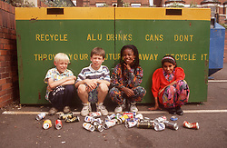 Multiracial group of young children recycling aluminium drinks cans; with recycling bins in background,