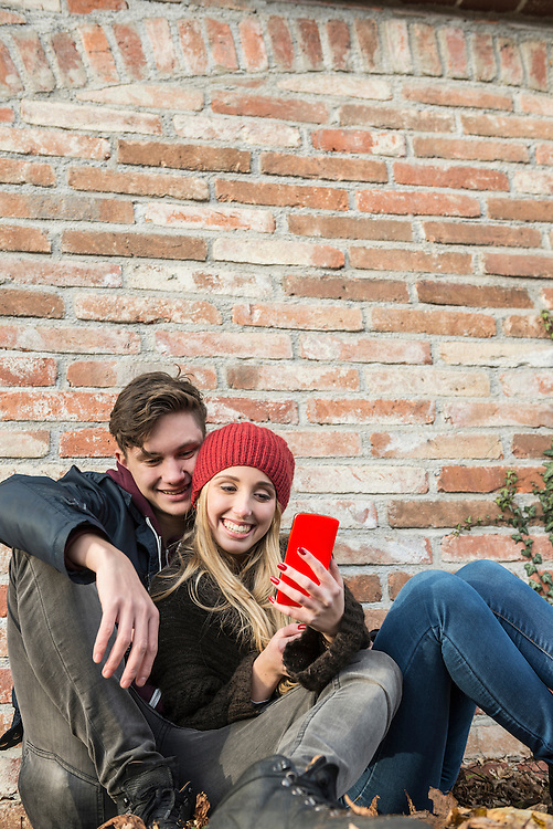 Young couple smiling and using smart phone against brick wall, Munich, Bavaria, Germany