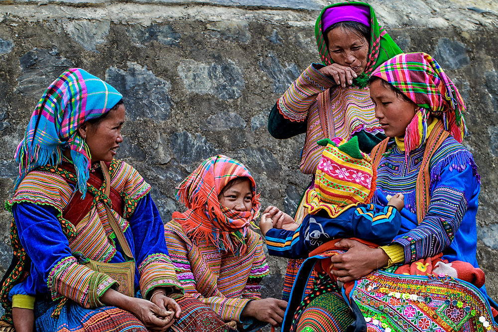 Flower Child:  A young mother and child hold court with their friends, all of the Flower Hmong tribe, in the morning market at Bac Ha, Vietnam.