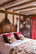 Interior of an English cottage with double bed in timber framed room