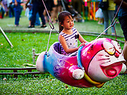 24 NOVEMBER 2018 - BANGKOK, THAILAND:  A girl rides a merry go round in the midway at the Red Cross Fair. The Red Cross Fair is a fund raiser and an annual event in Bangkok that draws thousands of attendees every night of its nine day run. The fair features games of chance, a midway with rides, handicrafts and food. This is the first year the fair has been in Lumpini Park. Previously it had been held in the Dusit section of Bangkok. The 2018 Fair marks 125 years of service for the Red Cross in Thailand. PHOTO BY JACK KURTZ
