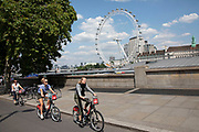 Tourists cycle past on Santander bike hire sheme bicycles across the river from the London Eye, one of the most famous landmarks, skylines and iconic buildings in the capital in London, England, United Kingdom. London Eye, also known as the Millennium Wheel.