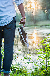 Mid section of a man standing with shoes in hand at lakeshore, Bavaria, Germany