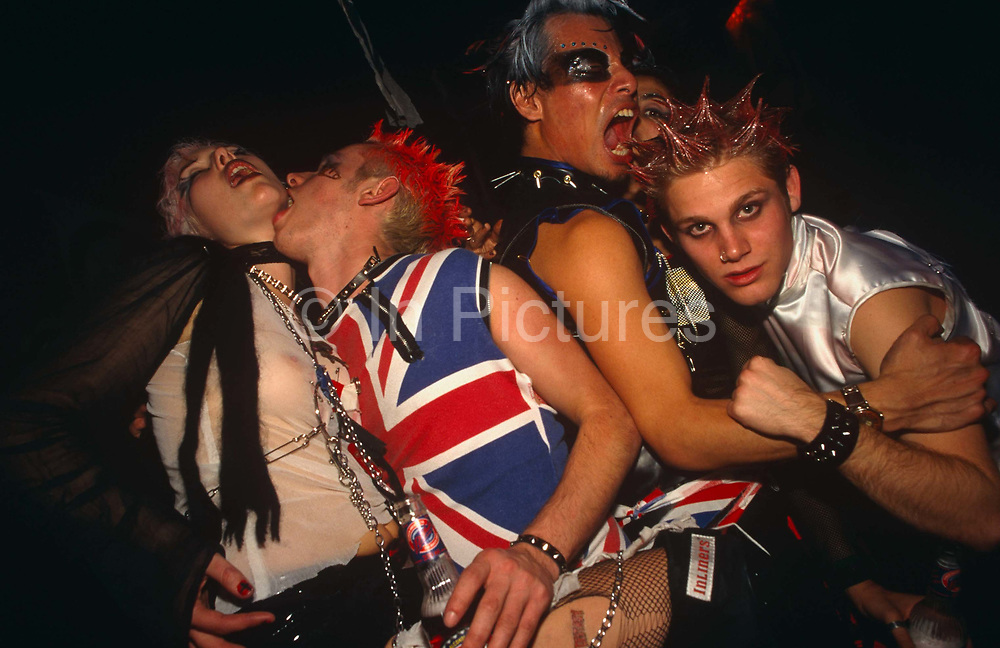 Four energetic party goers are dressed up as eccentric 70s punks at a Halloween event in Adrenaline Village, Battersea, London UK. Taken from below them with flash the group is in a dark club environment, their make-up is authentic-looking complete with hair gel and mascara.  They wear tights and a girl on the left has safety pins while being licked on the neck by a man. Another is wearing a Union Jack sleeveless T-shirt while one person is looking directly at the camera. They might look authentic but it has been 20 years since Punk was the huge youth culture of the day.