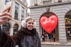 """© Licensed to London News Pictures. 14/02/2018. LONDON, UK. A tourist takes a selfie of a giant chubby heart balloon at The Ritz Hotel in Piccadilly as part of """"Chubby Hearts Over London"""",  a design project conceived by Anya Hindmarch.  Supported by the Mayor of London, the British Fashion Council and the City of Westminster giant chubby heart balloons will be suspended over (and sometimes squashed within) London landmarks as a declaration of love to the city starting on Valentine's Day and continuing throughout London Fashion Week.   Photo credit: Stephen Chung/LNP"""