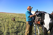 John Zeman adjusts the game strap on his saddle after finding a shed antler during a Montana prairie grouse hunt.