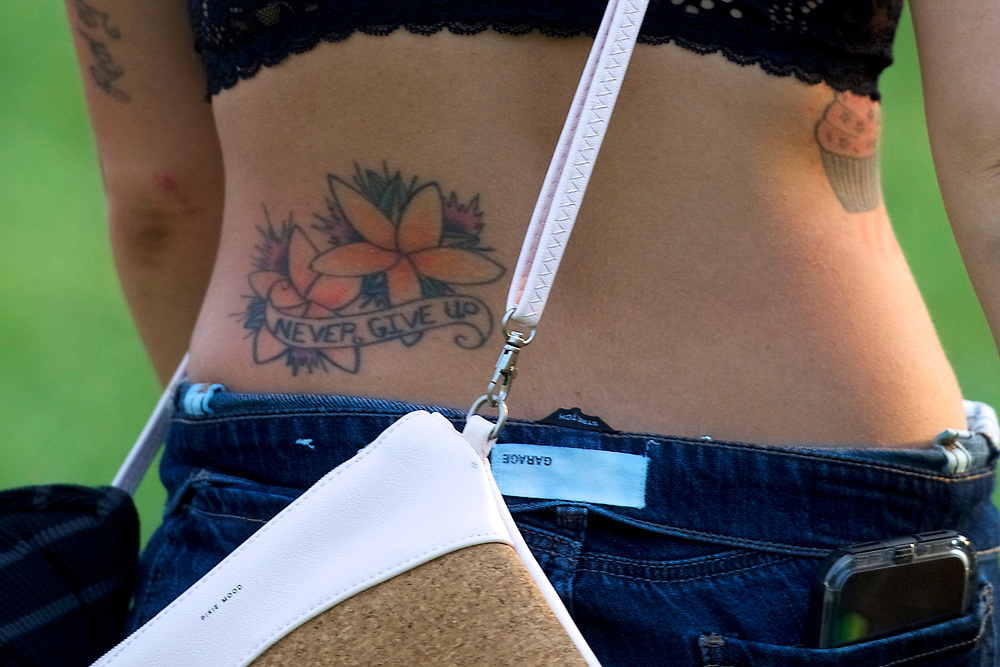 """A reveler with a tattoo stating """"NEVER GIVE UP"""" walks through the concert grounds on the second day of the Firefly Music Festival in Dover, Delaware U.S., June 15, 2018.  REUTERS/Mark Makela"""