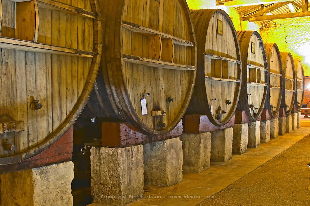 Chateau St Martin de la Garrigue. Languedoc. Barrel cellar. Wooden fermentation and storage tanks. Illuminated cellar. Wooden cross-beam roof. France. Europe.