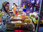 13 JULY 2013 - BANGKOK, THAILAND:  A Thai Muslim street food vendor makes food for Iftar (the Muslim meal that breaks the day long fast) during Ramadan. Ramadan is the ninth month of the Islamic calendar, and the month in which Muslims believe the Quran was revealed. The month is spent by Muslims fasting during the daylight hours from dawn to sunset. Fasting during the month of Ramadan is one of the Five Pillars of Islam. Muslims believe that the Quran was sent down during this month, thus being prepared for gradual revelation by Jibraeel (Gabriel) to the prophet Muhammad.        PHOTO BY JACK KURTZ