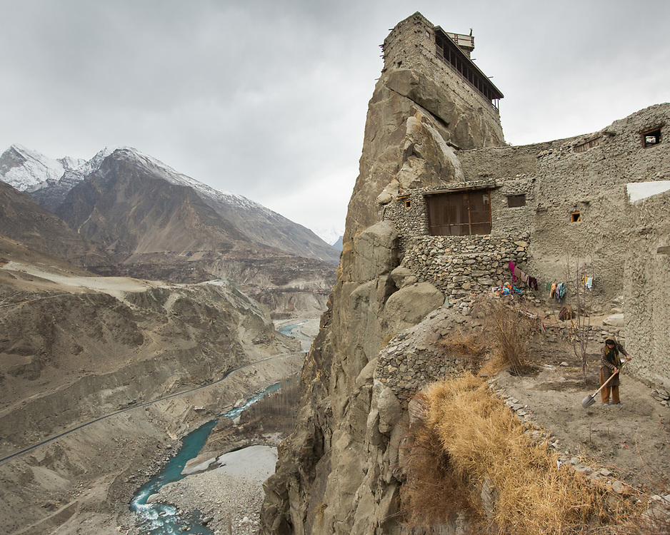 Below the Altit fort and above the Hunza river, a woman tends to her potatoe field. In the old fortified village of Altit, over 1000 years old, Hunza region.
