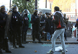 "French anti-riot policemen stand in front of migrants near the Jaures and Stalingrad metro stations, in northern Paris, France, on October 31, 2016, during a police operation aiming at a future evacuation of a migrant camp. An operation of ""administrative control"" was underway on early October 31 in the Jaures/Stalingrad quarter before a future evacuation, whose date has not yet been set, according to a police source. The makeshift camp on the outskirts of the 10th and 19th arrondissements in the north of the capital numbers today 2,500 people, according to the City of Paris. Photo by Somer/ABACAPRESS.COM"