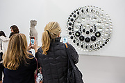 """New York, NY - 5 May 2017. The opening day of the Frieze Art Fair, showcasing modern and contemporary art presented by galleries from around the world, on Randall's Island in New York City. Two women take photos of Olafur Eliasson's """"Your hope diagram,"""" an assemblage of partially silvered crystal spheres and stainless steel in the Tanya Bonakdar Gallery."""