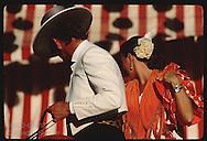 Couple in festival attire glance toward caseta tent atop horse at the Feria de Abril; Seville. Spain
