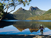 """A bushwalker admires Cradle Mountain reflecting in Dove Lake, in Cradle Mountain - Lake Saint Clair National Park, Tasmania, Australia. The Tasmanian Wilderness was honored as a UNESCO World Heritage Site in 1982, expanded in 1989. The most extensive dolerite formations in the world dominate the landscape of Tasmania, where magma intruded into a thin veneer of Permian and Triassic rocks over perhaps a million years during the Jurassic breakup of supercontinent Gondwana in the Southern Hemisphere, forming vast dolerite/diabase sills and dike swarms. (North American geologists use the term diabase instead of dolerite to refer to the fresh, unaltered rock.) Published in Wilderness Travel 2008 Catalog of Adventures. Published in """"Light Travel: Photography on the Go"""" book by Tom Dempsey 2009, 2010. For licensing options, please inquire."""