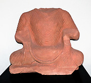 Torso of a seated Buddha AD 200-50 Kushan dynasty. Mathura, Uttar Pradesh, North India, Sandstone.  Some of the earliest images of the Buddha were created Mathura.  As with other early images, the Buddha's chest is fully expanded with yogic breath .  He wears an outer monastic robe drawn up over both shoulders.