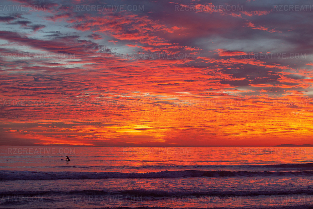 A surfer in the ocean with vibrant and colorful sunset.