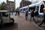 "Shot from the hip: Tiny ""Express Shuttle Bus"" van, two guys in stripey tops, a man whose case matches the tram and various signs of confusion and anxiety on a Saturday morning in Amsterdam."