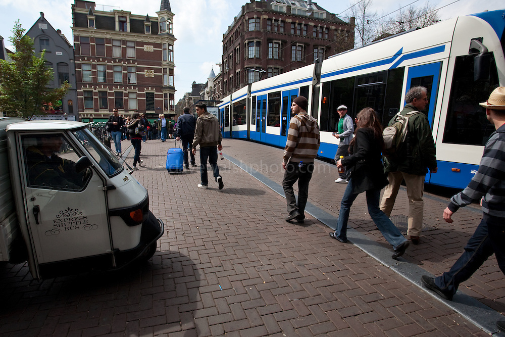 """Shot from the hip: Tiny """"Express Shuttle Bus"""" van, two guys in stripey tops, a man whose case matches the tram and various signs of confusion and anxiety on a Saturday morning in Amsterdam."""